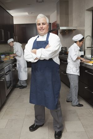 Proud : Chef stands with arms folded in blue apron and organised kitchen