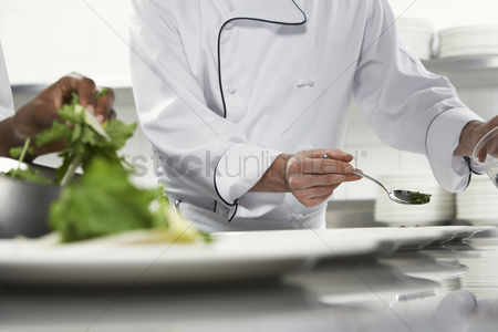 Bowl : Chefs preparing salad in kitchen mid section