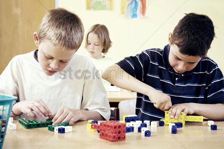 Enjoying : Children assembling plastic blocks in the classroom