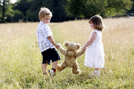 Grass : Children holding a teddy bear