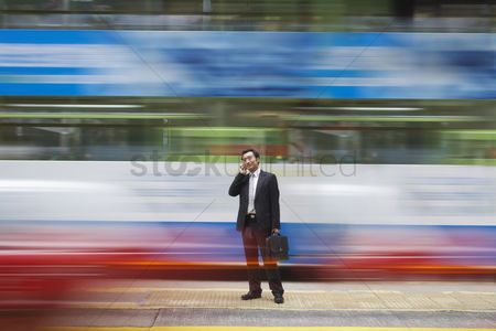 Black background : China hong kong business man using mobile phone standing on street long exposure