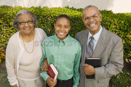 Religion : Christian grandparents and grandson in garden holding bibles portrait