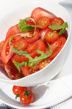 Bowl : Close  - up of sliced tomatoes with rucola