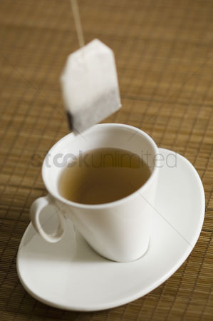Excited : Close-up of a cup of herbal tea on a saucer with a teabag