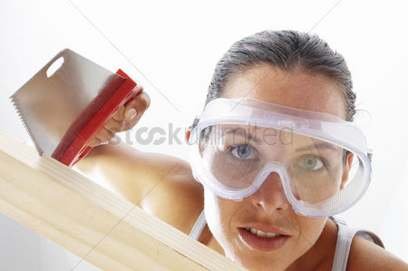 Goggle : Close-up of a woman with goggles sawing a wood