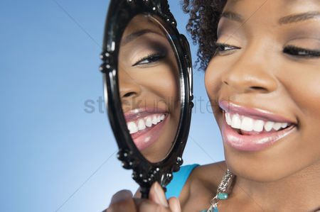 Curly hair : Close-up of a young woman looking at herself in mirror and smiling over colored background