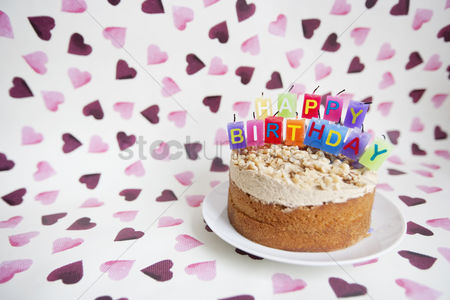 Shape : Close-up of birthday candles on cake over heart shaped background