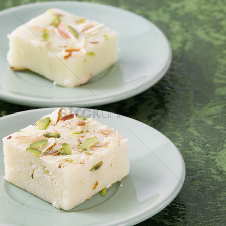 Almond : Close-up of burfi in saucers