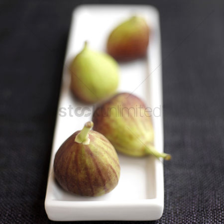 Appetite : Close up of four figs on a small plate