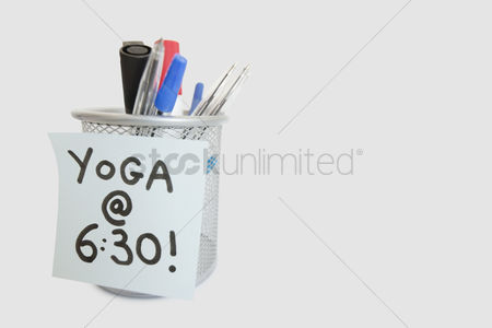 Collection : Close-up of sticky note with yoga message on pen holder over white background