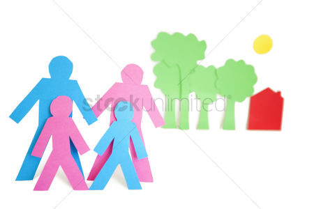Arts : Conceptual image of paper cut out shapes representing a family with trees and house over white background