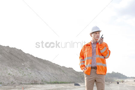 Supervisor : Confident male supervisor using walkie-talkie on construction site against clear sky