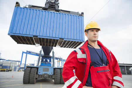 Forklift : Confident male worker standing in front of freight vehicle at shipyard