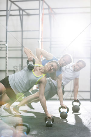 Muscle training : Confident people exercising in crossfit gym