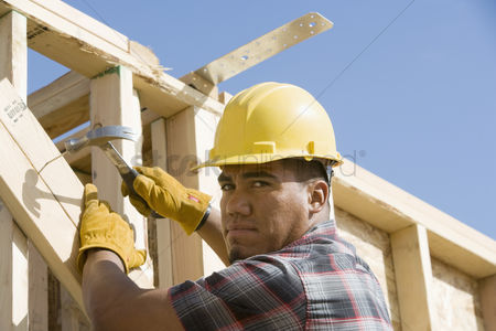 Expertise : Construction worker using hammer on building