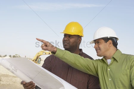 Gesturing : Construction workers reading blueprints