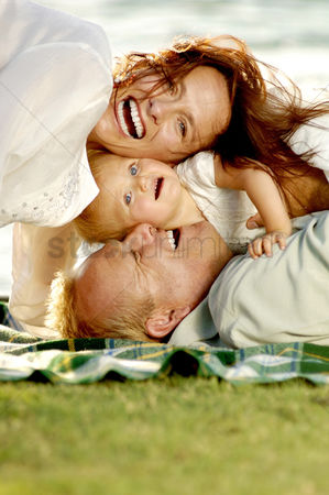 Grass : Couple and their lovely daughter having fun in the park