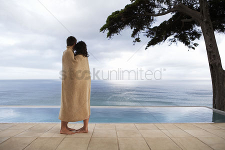 Love : Couple covered in towel standing by infinity pool side view