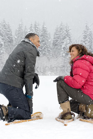 Employment issue : Couple crouching in the snow wearing snowshoes