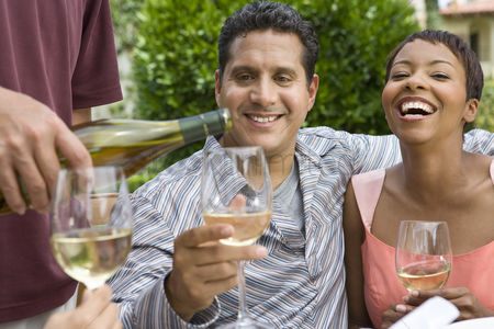Wine bottle : Couple drinking wine with friends outdoors