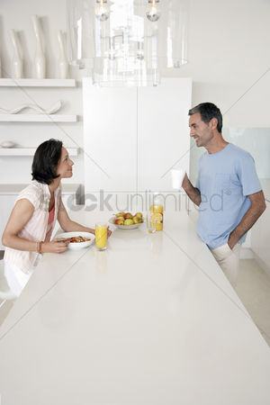 Pocket : Couple eating breakfast at kitchen bench side view
