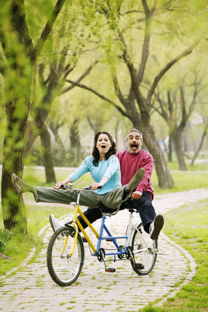 Husband : Couple having fun cycling in the park