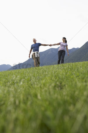British ethnicity : Couple holding hands grass in foreground
