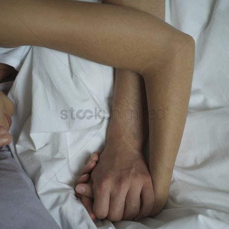 Husband : Couple holding hands while sleeping on the bed