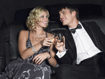Toasting : Couple in back of car drinking champagne