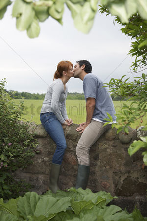 Relationships : Couple kissing on wall in countryside