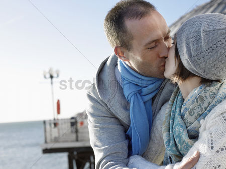 Kissing : Couple kissing standing on pier head and shoulders