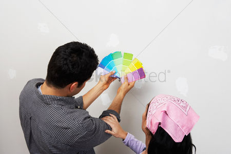 Arts : Couple looking at paint samples near interior wall back view elevated view