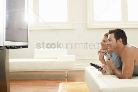 Furniture : Couple lying on bed watching plasma tv together side view