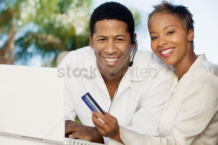 Shopping : Couple on patio making online credit card purchase portrait