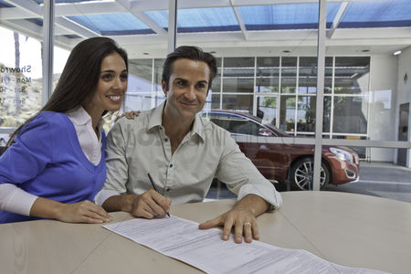 Land : Couple signing documents for new car