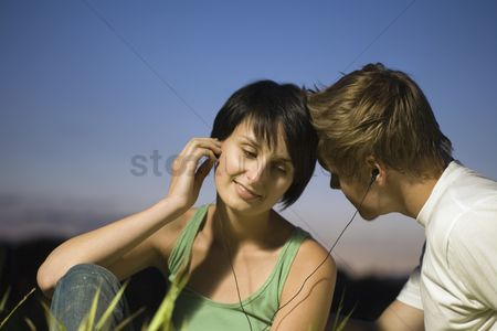 Earphone : Couple sit listening to music on shared earphones