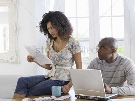 Bald : Couple sitting at table using laptop and reading document