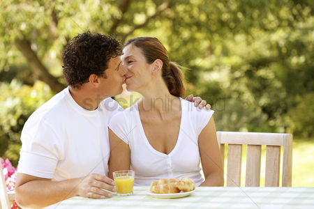 Outdoor : Couple sitting at the picnic table kissing