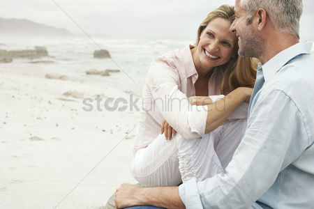 Husband : Couple sitting on beach smiling