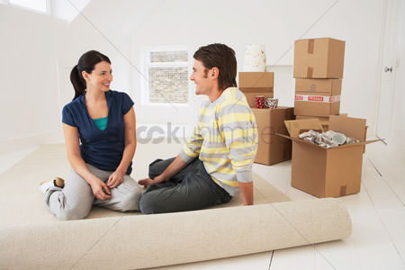 Couples : Couple sitting on half-rolled carpet in new home