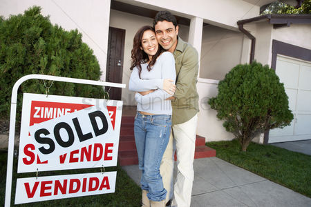 Relationships : Couple standing in front of house with sold sign portrait