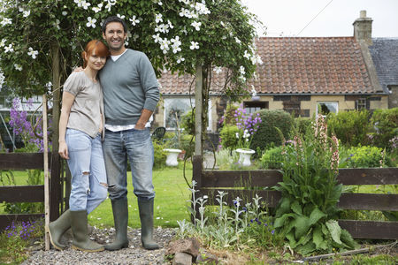 Denim : Couple standing outside house in countryside portrait