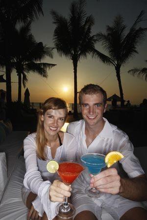 Toasting : Couple toasting cocktail during sunset