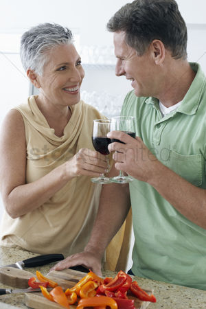 Toasting : Couple toasting wine in kitchen