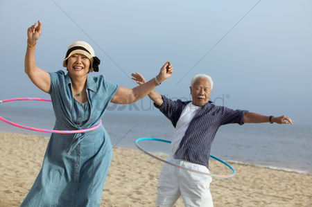 Retirement : Couple with hula hoops on beach