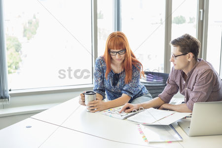 Three quarter length : Creative business colleagues reading file together at desk in office