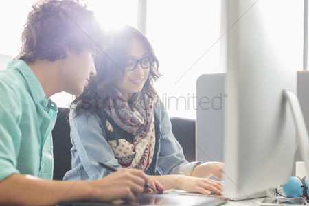 Women : Creative business colleagues using desktop computer in office
