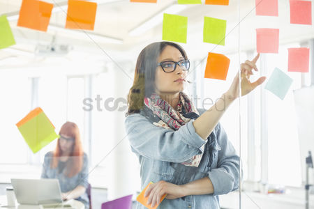 Two people : Creative businesswoman reading sticky notes on glass wall with colleague working in background at office