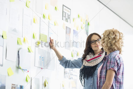 Women : Creative businesswomen discussing over papers stuck on wall in office