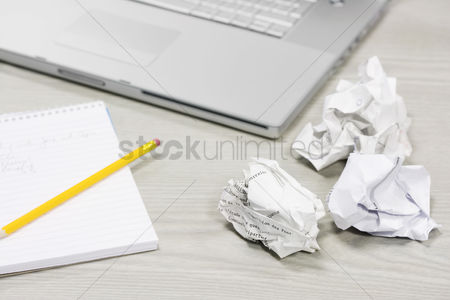 Notebook : Crumpled paper and notebook on desk by laptop close up